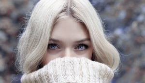 a woman with beutiful skin looks through her sweater