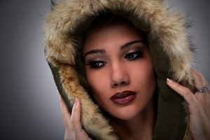 a woman with a beautiful face and hood on stares gently in the distance