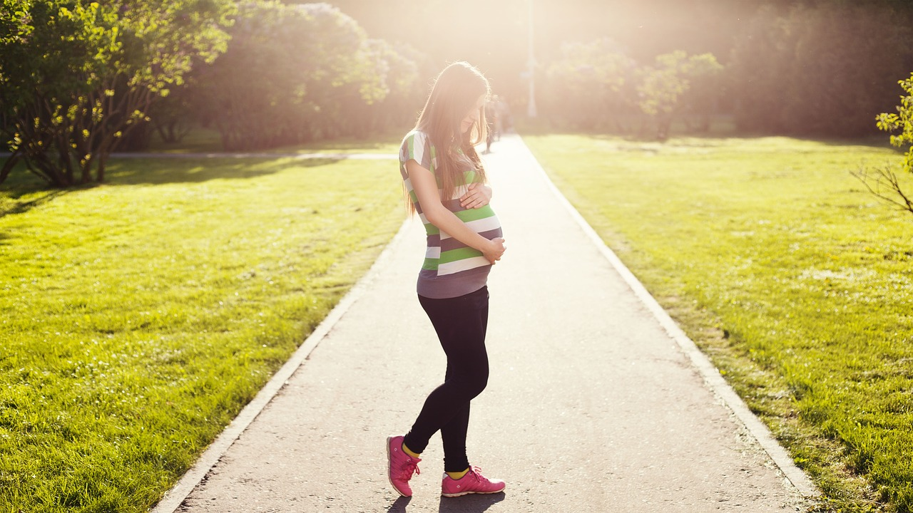 pregnant woman holds her belly as she walks