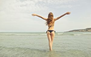 a woman proudly displays her new bikini body