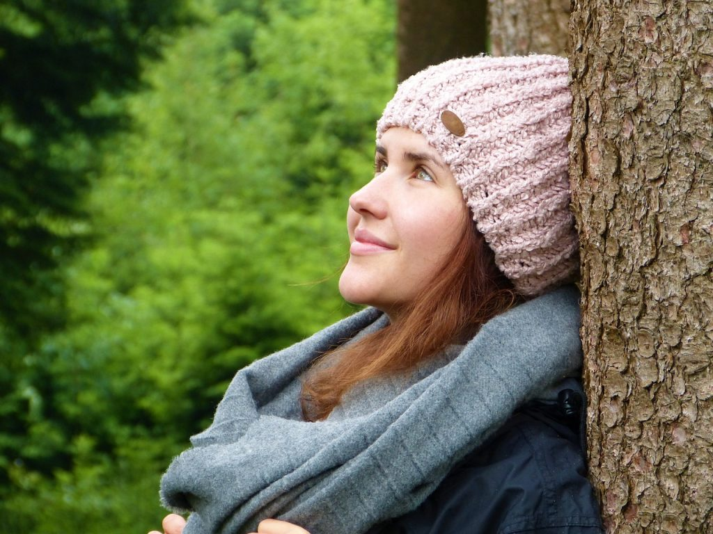 a beautiful woman stands with her back to a tree