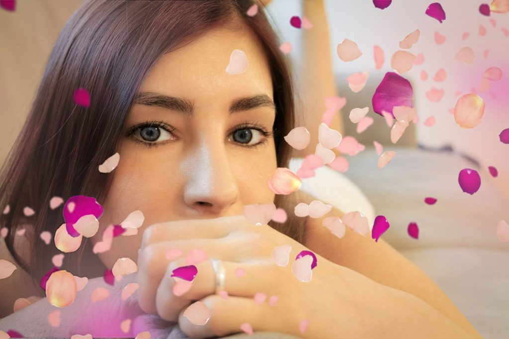 a model stares at the camera with rose petals floating in the frame