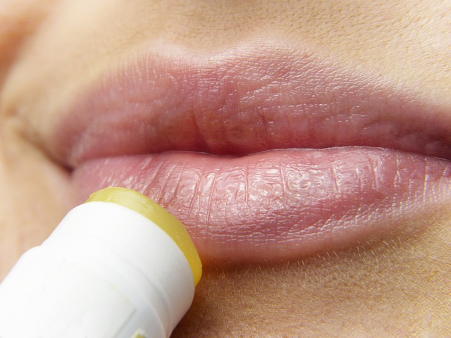 a woman applies lip balm